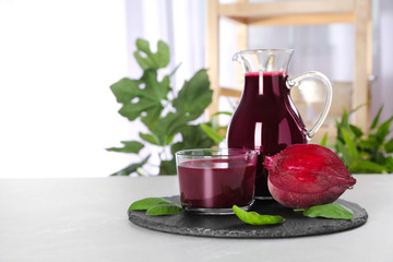 Jug and glass of fresh beet juice on table