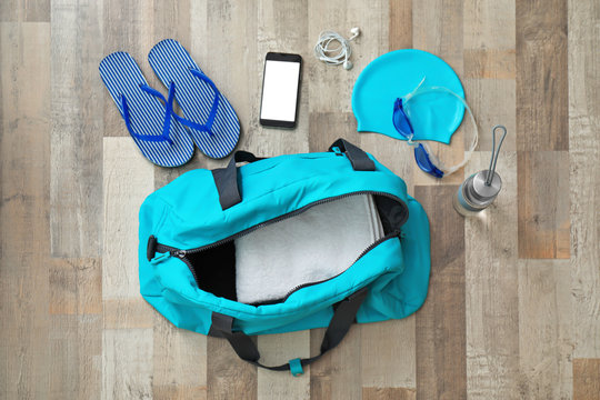Flat lay composition with sports bag and equipment for swimming pool on wooden floor, top view