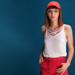 Fashionable redhead girl in red cap and eyeglasses.