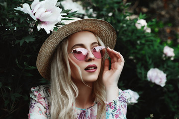 Beautiful young woman wearing pink cat eye sunglasses, straw boater hat posing in the blooming garden. Model looking up. Female spring fashion concept