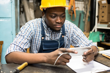 Content concentrated handsome young African-American factory worker in yellow hardhat using smartphone in earphones to watch educational video and sitting at table in dark shop.