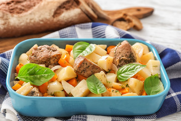 Casserole with tasty meat and potatoes on table