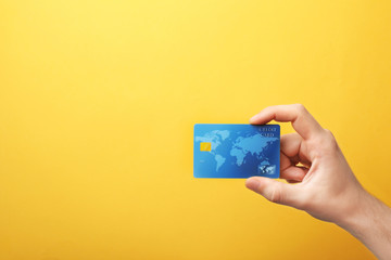 Young man holding credit card on color background