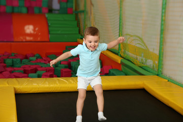 Cute boy jumping on trampoline in entertainment center