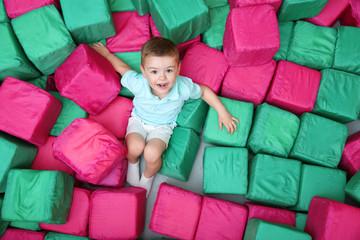 Cute boy playing among soft cubes