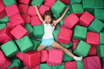 Cute girl playing among soft cubes