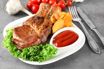 Plate with delicious grilled ribs, vegetables and sauce on table