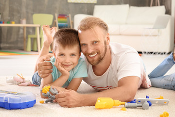 Father playing with cute son at home