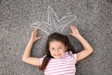 Cute little girl lying on asphalt, outdoors