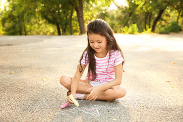 Cute little girl drawing with chalk on asphalt, outdoors