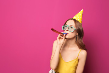 Young woman with party blower on color background. Birthday celebration