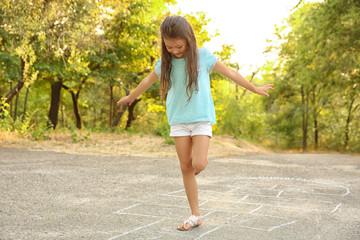 Cute little girl playing hopscotch, outdoors