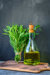 Fresh garden bunch of rosemary with a bottle of rosemary oil or olive oil on cutting board over stone background.