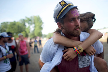 Ryan Chatfield, 26, carries his wife's sister who had too much to drink on the fourth and final day of the Firefly Music Festival in Dover