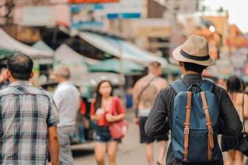 Young man traveling with hat, Asian hipster traveler walking at famous backpacker street in Bangkok (Khao San road), landmark and popular for tourist attractions in Thailand. Travel concept