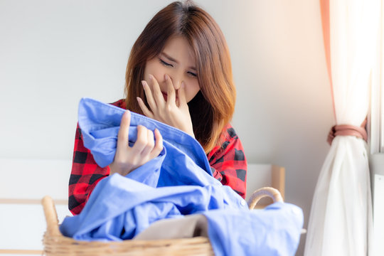Portrait beautiful housewife. Attractive beautiful asia woman is smelling stinky, musty from her husband shirt. Asian woman will bring shirts for washing at laundry room. She use fingers close nose