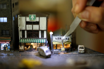 Taiwanese artist Hank Cheng poses with his miniature model of street scenes, in New Taipei City