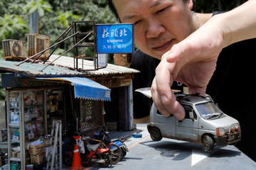 Taiwanese artist Hank Cheng poses with his miniature model of Taipei street scenes, in New Taipei City