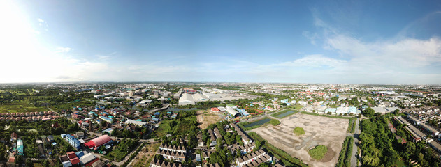 Aerial view above the industrial estate town overlooking factories and housing estate on a clear blue sky day