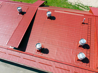 new red metal warehouse roof with installed pipes of ventilation systems