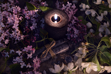 Lilac spring flowers with burning black candle. Occult, esoteric and divination still life. Halloween background with vintage objects and magic ritual