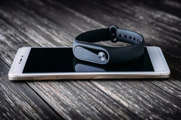 Black fitness tracker on white smartphone