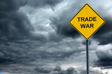 road warning sign with text trade war in front of storm cloud