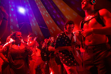 (C) Cooper Cuje, 20, dances in a silent disco on the fourth and final day of the Firefly Music Festival in Dover, Delaware U.S.