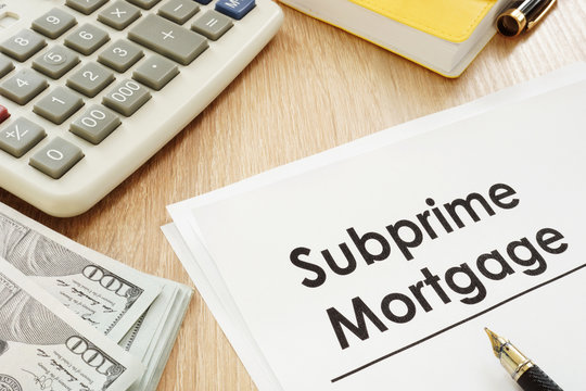 Subprime mortgage form, calculator and pen.