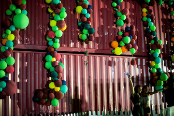 A pair of revelers pose for a portrait beside a stacked crate of cargo containers with balloons before departing on the fourth and final day of the Firefly Music Festival in Dover, Delaware U.S.