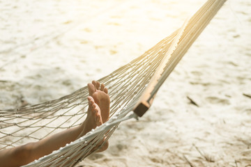 Woman relaxing in the hammock at the beach.