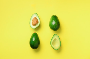 Organic avocado with seed, avocado halves and whole fruits on yellow background. Top view. Pop art...