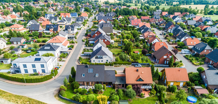 Typical German new housing development in the flat countryside of northern Germany between a forest and fields and meadows