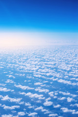 View of blue sky above the clouds from airplane window