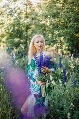 Beautiful young girl in the flowers of lupine. Girl with blonde hair in a long dress with a bouquet of flowers