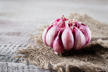 Garlic on rustic napkin on wooden backgrund table. Copy space