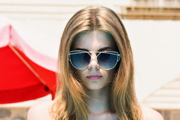 Girl in retro glasses. Beauty woman portrait of teen european girl beautiful cheerful enjoying summer sun with long brown hair and clean skin