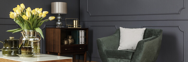 White pillow on a velvet green armchair and a wooden cabinet by a gray wall with molding in a classy living room interior. Real photo.