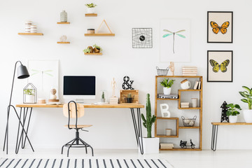 Modern home office interior with a wooden desk, chair, shelves, computer with empty screen and plants