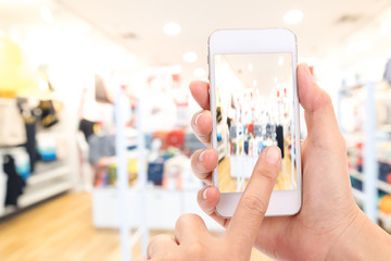 Woman hand Taking a picture with a smart phone in shopping mall with blurred image of clothes shop.