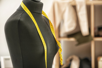 Tailor's mannequin with measuring tape in atelier