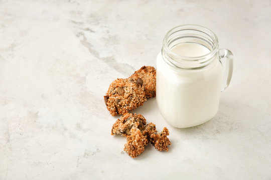 Delicious oatmeal cookies and mason jar with milk on light background