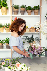 Creativity in work. Nice skillful florist looking at the flower bouquet while enjoying her work