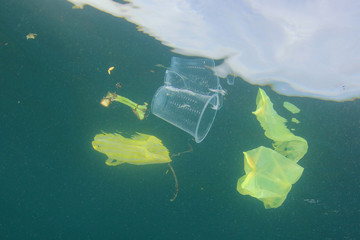 Plastic carrier bags and cups pollution in ocean