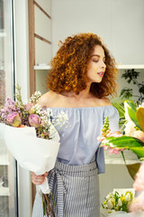 Interesting profession. Nice attractive woman standing in the flower shop while working as a florist