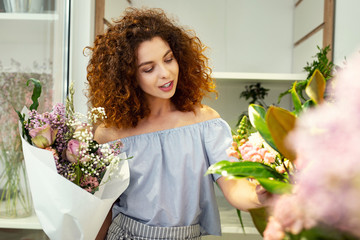 Beautiful tenderness. Delighted nice woman looking at the flowers while admiring their tenderness