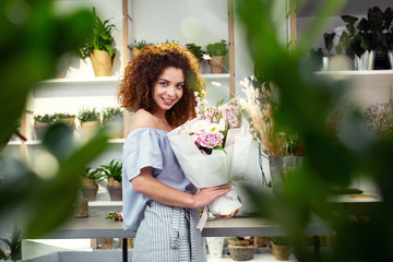 Beautiful bouquets. Joyful attractive woman choosing flowers while holding a beautiful bouquet