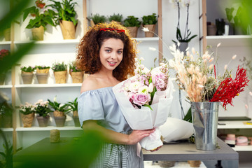 Female paradise. Delighted nice woman holding a bouquet while visiting a flower shop