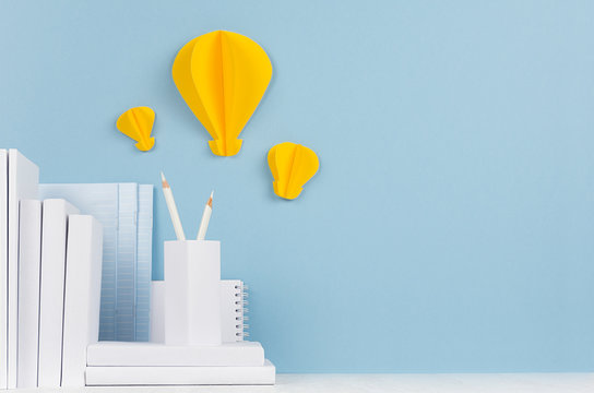 School template -  white books, stationery, decorative paper yellow lightbulbs origami on white desk and soft blue background. Back to school background with copy space.