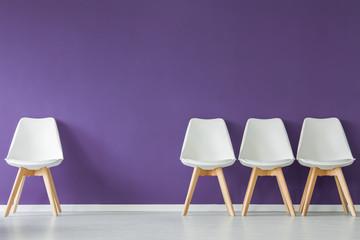 Chairs on purple wall